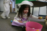 DLM6073  Gianna Asti, 2, of Louisville stoops over her Easter basket and looks over her goodies...