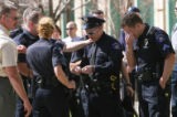 Aurora Police officer and Justin Grizzle, cq, (center with hat), is comforted by fellow officers...