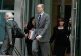 Justice Department litigators Leo Wise,(c)  and Colleen Conry, (l), leave in the 2nd week of trial...
