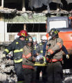 A demolition worker is rescued by Denver firefighters from the former Rocky Mountain News Building...