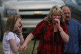 Friends of the Brock family (who did not want to be identified)  cry as they see a picture of...
