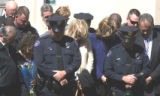 Heads are bowed during a prayer at a public memorial service for fallen Aurora Police Officer Doug...