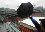 MAEA103 - A fan uses his umbrella to point something out at Fenway Park in Boston Thursday, April...