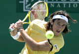 HTT103 - Juan Monaco, of Argentina, returns a shot to American Amer Delic in the second round of...