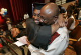 A proud Sharia V. Dixon is hugged by her father Leo Hood after she received her diploma during...
