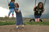 DLM0842  Laura Reed pushes her daughters Jessica, 4, left, and Sarah, 8, as they swing on the...