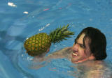 Standley Lake High School Junior Geoff Sweeney (cq) picks up a pineapple from the high board at...