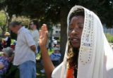 Christine Uwizera-Coleman (cq), of Denver, raises a hand in prayer during the National Day of...