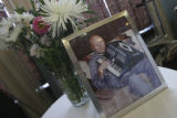 The memorial photo of Jack at upon a table with flowers adjacent and one of his accordians below....