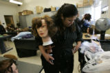 0033 Sonia Luna, CQ, 33, mother of three, works with a mannequin as she attends cosmetology class...