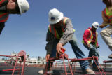 (L-R) Jose Saenz (cq) center,  measures forms being set for a concrete paver on the high speed...