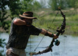 Armed with a fishing arrow, Gary Hague draws his bow and takes aim at a cruising carp. (ED...