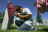 5th-grader Tony Silva (cq), of Trailor Academy, bows his head after placing a flag in front of a...