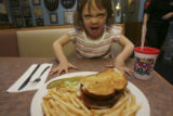 Lily Reynoso, 4, attacks a Wopburger at the Blue Parrot restaurant in Louisville, Colo. on Friday...