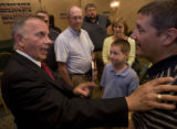 U.S. Congressman Tom Tancredo talks with Darran Whiting (right) after a town hall style meeting in...