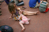 5 year-old Finn O'Sullivan (cq) rests her head on her mother's lap. Lisa Holmes (cq) and her...
