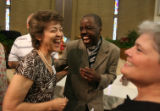 DLM0997  Reverend Paul Neshangwe, center, shares a laugh with Joann Briggs, left, and Sue Briggs,...