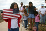 Sarah Appleton, 5 years old from Arvada, left, holds an American flag in memory of her...