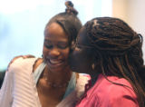 L to R: Alicia Taylor (cq) gets a kiss from her foster mom, Cherry Charles (cq) during a...