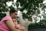 Ann Golightly (cq), holds her daughter Kaylee Golightly (cq), 17 months, as they wait for her...