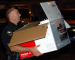 Grand Junction Police Officer Adam Winch removes a printer early Wednesday May 16, 2007 used in a...