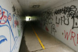 DLM0204  A bicyclist rides through the bike path tunnel where Elsha Juel and her 2-year-old son...