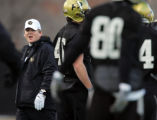 New University of Colorado football coach Dan Hawkins (left) keeps a close eye on practice as he...