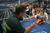 Denver Broncos coach Mike Shannahan (cq) grabs the finger of 9 month-old Reyna Gallegos (cq), as...