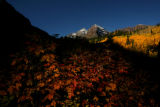 The snow-capped Maroon Bells light up as the sun rises, in the Maroon Bells Wilderness Area, near...