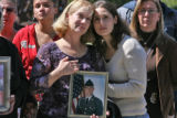 L to R: Michelle Martin (cq) and daughter Adrienne Martin (cq) hold a photo of (s0n & brother)...