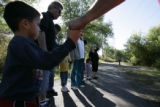 Neighbors from the neighborhood near where Niveah Gallegos' body was found, pray the Lord's Prayer...