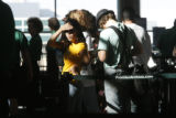 Passenger Doni Curkendall (cq) of Boulder scans for an open attendant while in the ticket line at...