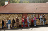 Tourists at the Pikes Peak Cog Railway point at and take photos of a wildfire burning on the...