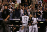 Colorado Rockies Garrett Atkins receives high-fives after scoring for the Rockies, to make it 2-4...