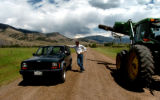 (DILLON Colo., July 14, 2004) Scott Hummer (in jeep) talks to Benson Ranch manager Mark McAllister...