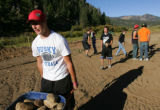Junior Michael Pollick (cq), 16, carries a wheel barrow filled with rocks as a group of Platte...