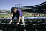 DM0023 Dick Mallory, 78, wipes down seats at Coors Field prior to the start of the Colorado...