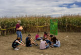 "A group of kids sit eating popcorn after completing the Anderson Farm's ""Pirates of the..."