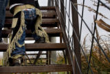 Three-year-old Ben Hunt (cq), works hard to hike up the stairs of a bridge while wearing chaps in...