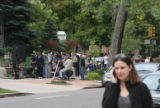 A small scene is being filmed in the background as an unidentified person passes by on a...
