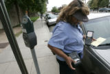 Bonnie Medina (cq) a Denver Vehicle Control Agent, writes tickets on Bannock near the City and...