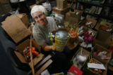 "Bette Ann Jaster, OP, (cq), in her creative space, holds ""Peace Planet"", by Mary Ellen..."