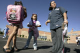 Adriana Hernandez (cq) picks up her children Maria, 8, left and Katy , 6 , middle, at the end of...
