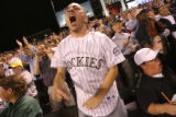 Phil Kaplan (cq) supports his team as the Rockies stay in the game against  the San Diego in the...
