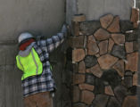 A worker puts up stone on the side of a large parking structure, Thursday morning, October 4,...