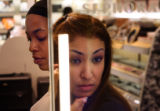 (at right) Maria Dominguez (cq) looks at her freshly applied eye shadow, as Alancia Unser (cq)...
