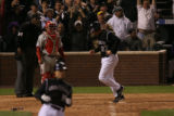 Colorado Rockies Garrett Atkins crosses home plate after a single by Jeff Baker, making the score...