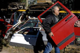 DM0477     Dave Crespin, 71, co-owner of B.J.'s Used Jeep Parts carries a used door to a Jeep...