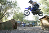DM0010     Malachi Cowan jumps his motorbike in front of his house on W. 13th Avenue just west of...