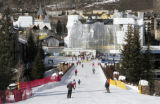 Skiers ski across the bridge towards the new construction of the ArraBelle at Vail Square, in the...